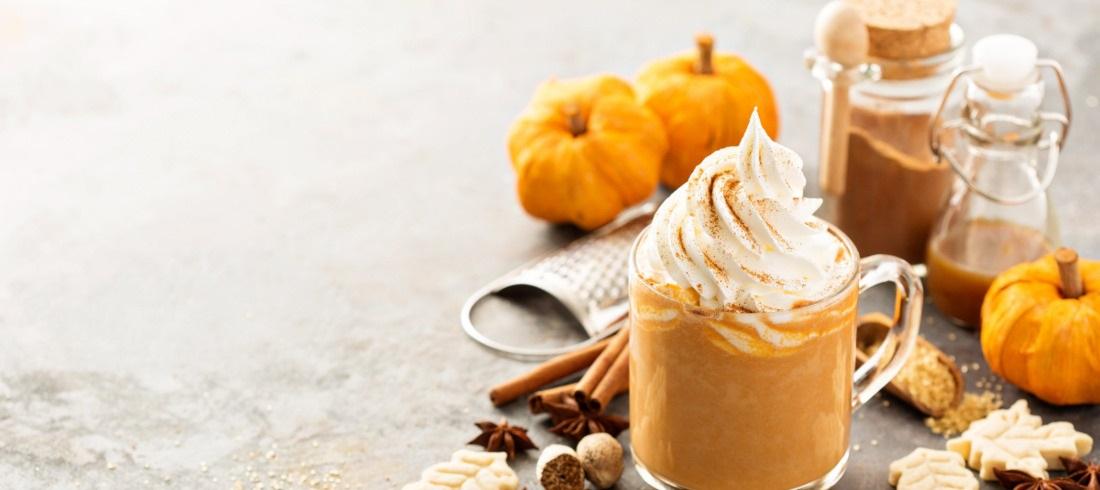 fall items including a mug of pumpkin spice, pumpkins, cinnamon